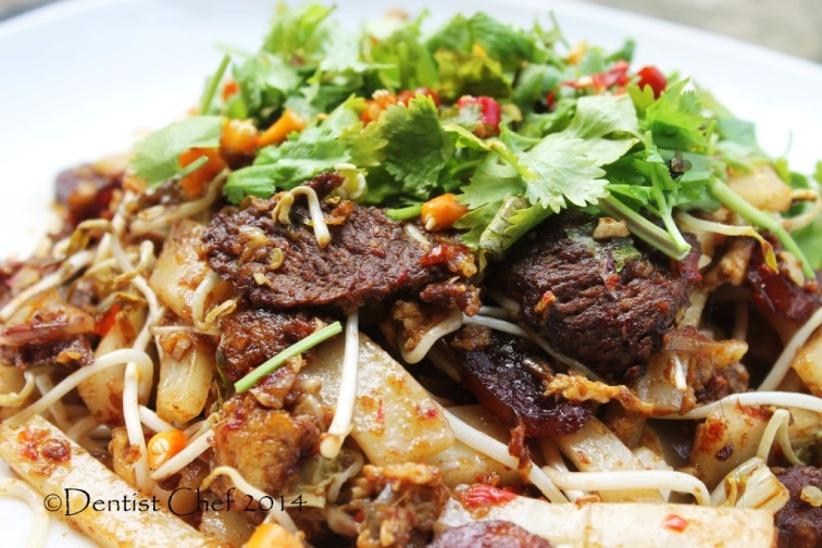 char kway teow with wagyu beef xo sauce asian rice noodle  beansprout chili egg chinese sausage lap cheoung cilantro